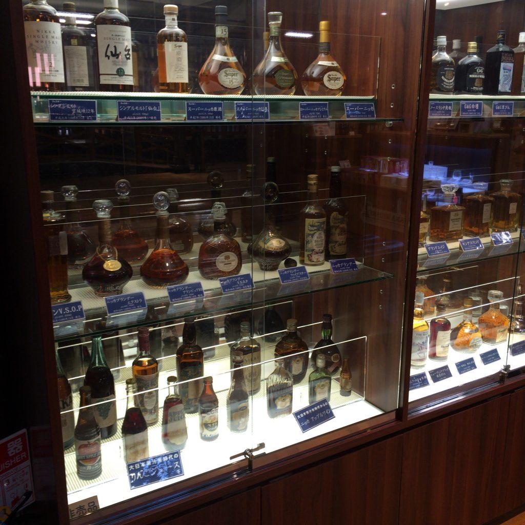 宮城峡蒸留所にある、ニッカのボトルのディスプレイ。よく見ると、ウイスキー以外にブランデーやアップルワインといった商品があることがわかります。カフェ式蒸留器によって生み出された商品も多数。