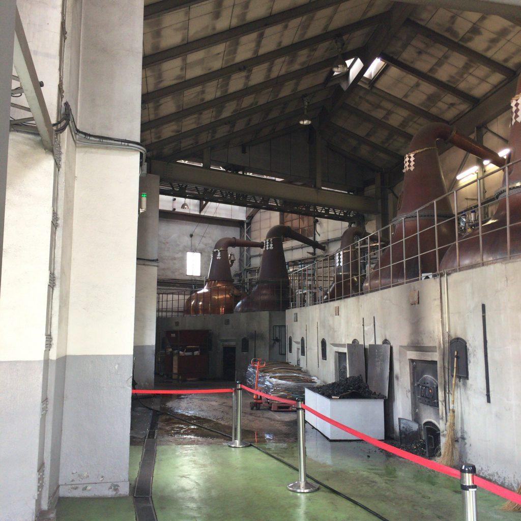 余市蒸留所のポットスチル群。真ん中の小さい蒸留器が第一号蒸留器。足元にあるのは補助燃料として使われる樽の廃材。
